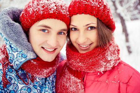 winterwear: Portrait of happy young woman and her boyfriend looking at camera in winter park