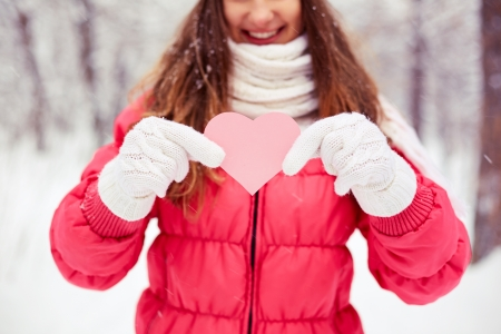 winterwear: Close-up of girl showing pink paper heart