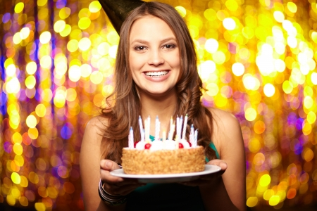 birthday adult: Portrait of joyful girl holding birthday cake and looking at camera at party Stock Photo
