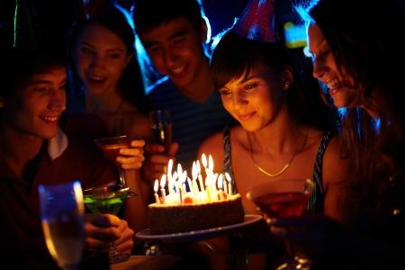 torta con candeline: Ritratto di ragazza gioiosa guardando la torta di compleanno circondato da amici alla festa Archivio Fotografico
