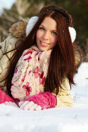 attractive gorgeous: Portrait of happy girl lying on snow and looking at camera