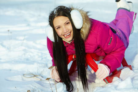 january 1: Portrait of happy girl lying on sledge and looking at camera