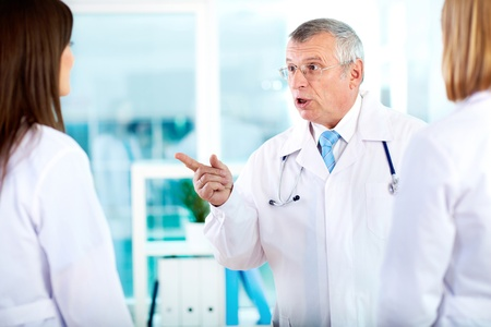 Portrait of mature doctor pointing at one of young clinicians while talking to her in hospital Stock Photo - 17086856