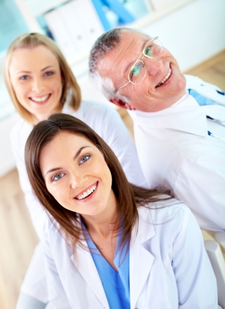 doctors smiling: Portrait of group of happy practitioners looking at camera Stock Photo