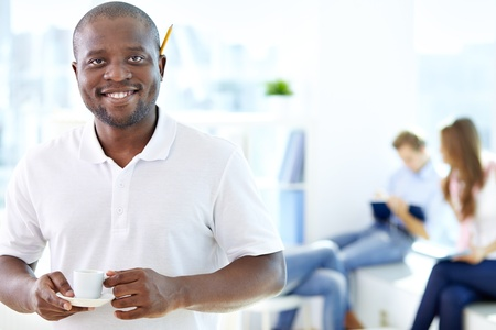 Portrait of happy African guy with cup looking at camera in working environment Stock Photo - 17087533