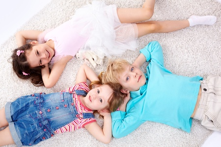 fellows: Three kids lying on the floor and looking at camera Stock Photo