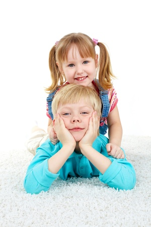 brothers and sisters: Two kids lying on the floor and looking at camera Stock Photo