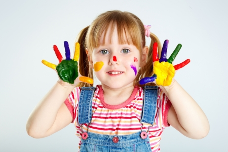 face paint: Girl having fun, her face and palms covered with paint Stock Photo
