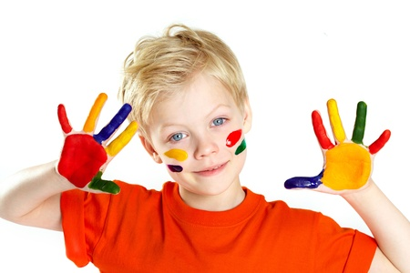 kids painted hands: Boy looking at camera with his palms and face covered with paint