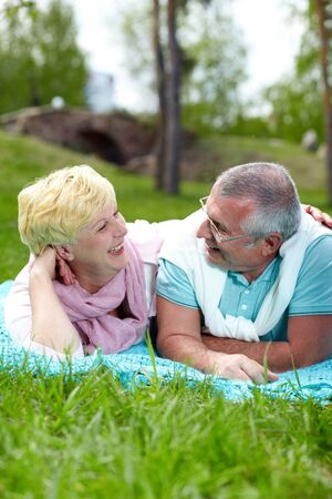 Happy mature couple lying on grass and looking at one another in the countryside photo