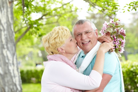 kiss couple: Happy mature woman with blooming bouquet kissing her husband in park