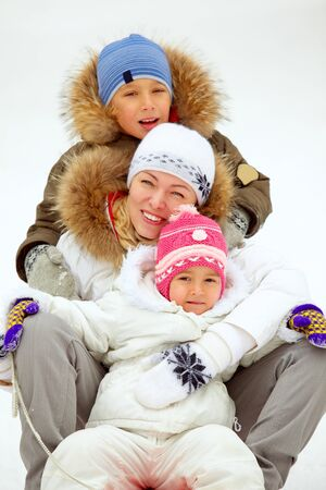 Happy kids and their mother sitting on sledge in park Stock Photo - 17088322