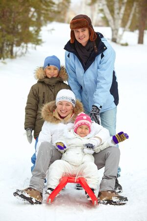 Happy kids and their parents tobogganing in park Stock Photo - 17086709