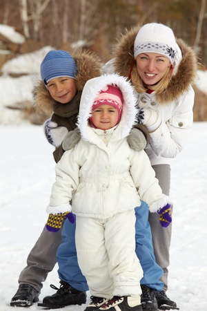 Happy kids and their mother in winterwear looking at camera Stock Photo - 17087727