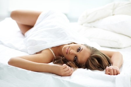 maquillage: Beautiful woman lying in bed and looking at camera