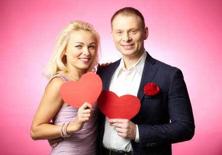 Portrait of elegant happy couple holding paper hearts Stock Photo - 17086899
