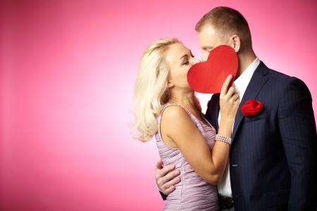 parejas de amor: Dos fechas j�venes bes�ndose detr�s de coraz�n de papel