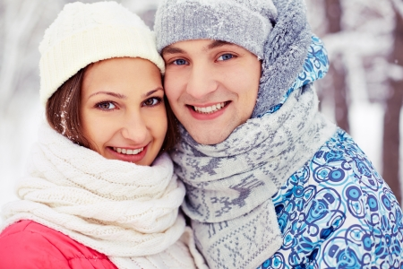winterwear: Portrait of happy young woman and her boyfriend in winter park  Stock Photo
