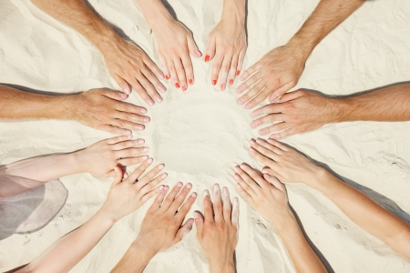 joined hands: Circle of hands of friends on sand Stock Photo
