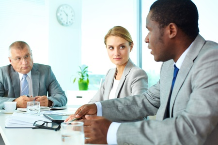 Portrait of pretty secretary and boss looking at employee at meeting Stock Photo - 17154115