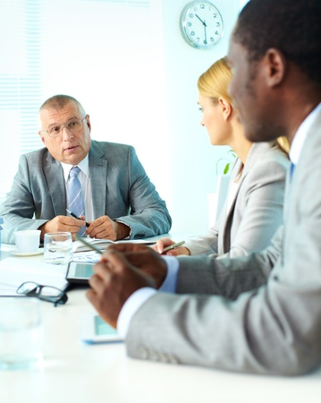 Portrait of smiling senior boss looking at his employees at meeting Stock Photo - 17154191