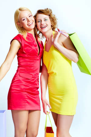 Two beautiful shoppers with paperbags over white background Stock Photo - 17154246
