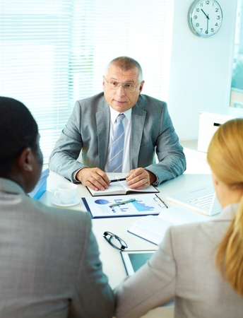 Portrait of mature boss looking at his employees at meeting Stock Photo - 17154158