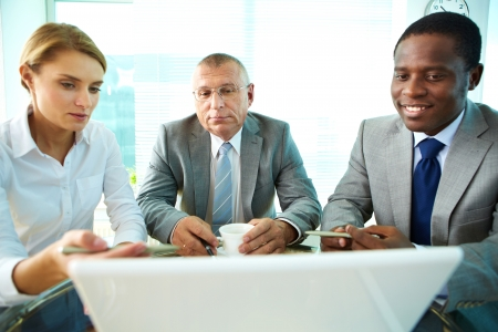 Portrait of business partners looking at laptop screen while female explaining something to her boss and colleague Stock Photo - 17148207