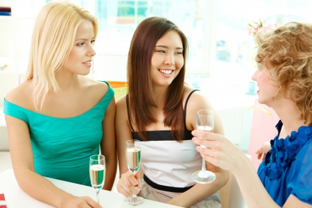 Gorgeous girls with flutes of champagne having talk photo