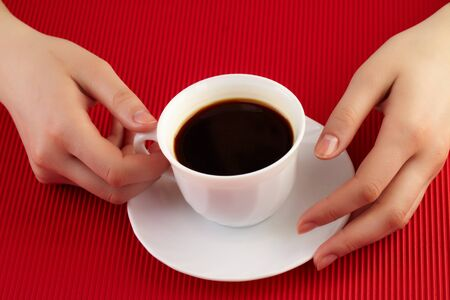 female hands holding porcelain cup of coffee photo