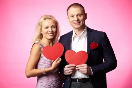 Portrait of elegant happy couple holding paper hearts and looking at camera Stock Photo - 17154196