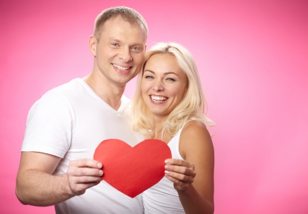 Portrait of happy couple showing red paper heart Stock Photo - 17154317