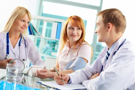 Portrait of confident practitioners and patient interacting in hospital Stock Photo - 17154241