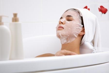 facial mask: Image of serene woman with facial mask enjoying bath in spa salon