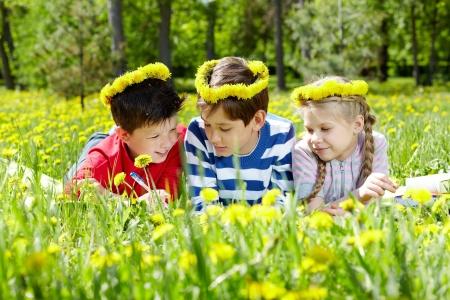 Three children with dandelion wreaths having rest on grass Stock Photo - 17154118