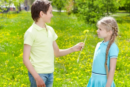 Little boy giving yellow dandelion to cute girl outdoor  Stock Photo - 17154152