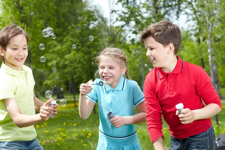 Three happy friends blowing soap bubbles outside  photo