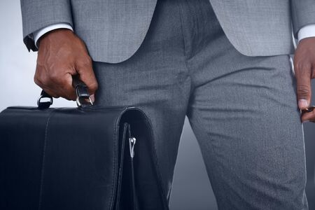 Close-up of businessman with briefcase in hand isolated on grey background photo