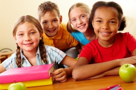 Portrait of smart schoolchildren looking at camera in classroom photo