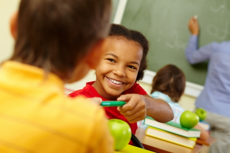Portrait of cute girl giving crayon to classmate at lesson photo