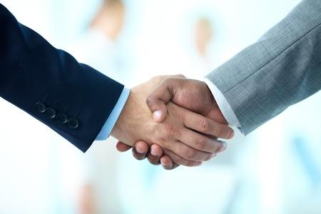 그들의 협력 관계를 확인하기 위해 손을 흔들면서 비즈니스 사람들의 근접