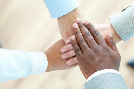 compa�erismo: La vista por encima de un equipo de negocios acumulan las manos en se�al de compa�erismo