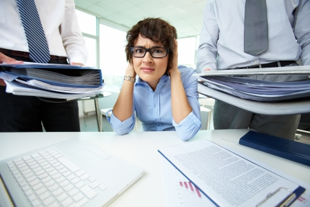 Office lady being scared because of too much paperwork to do photo
