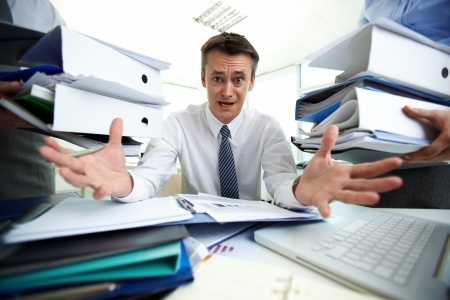 Desperate businessman not knowing what to do with all\ paperwork