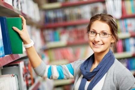 choose university: Portrait of pretty girl in library looking at camera with smile