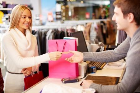 contadores: Retrato de la mujer bonita que da su tarjeta de cr�dito para hacer compras asistente mientras que el pago de su compra