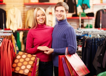 Portrait of amorous couple of shoppers looking at camera with smiles photo