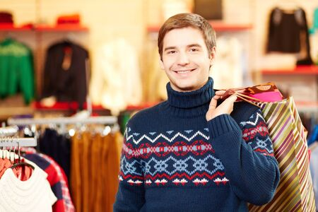young fellow: Portrait of happy man with paperbags looking at camera during shopping Stock Photo