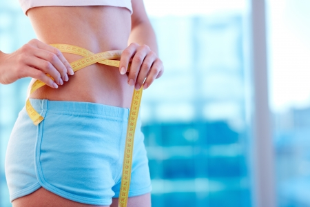 losing weight: Close-up of a woman in sportswear measuring her waist Stock Photo