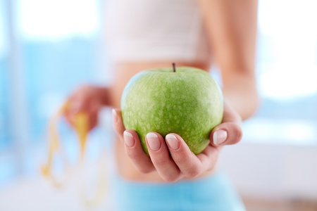 shallow focus: Close-up of a fit woman holding a fresh apple Stock Photo